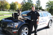 Police officer and K-9 with patrol car