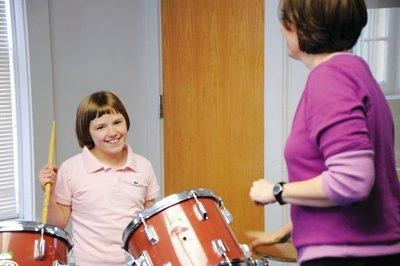 Girl playing drums while woman watches
