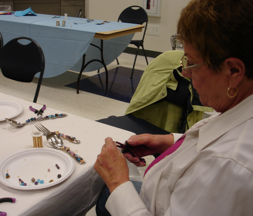 Craft activity adding beads to utensils